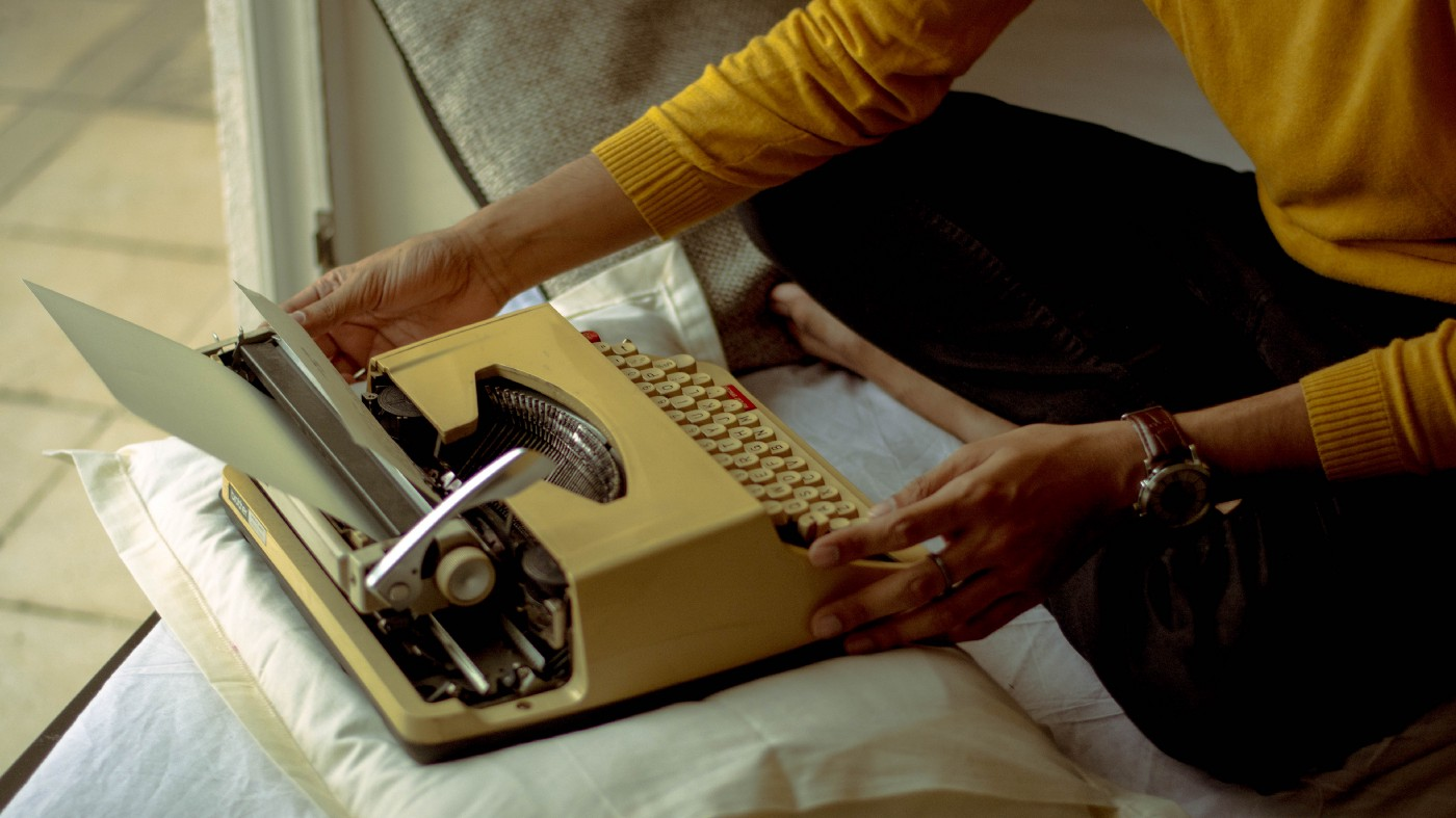 Someone wearing a yellow sweater using a type writer on top of a pillow
