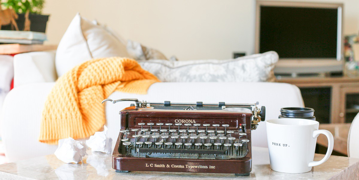 Corona typewriter on table with crumpled pieces of paper beside it, a white sofa and yellow blanket behind, and a coffee mug.