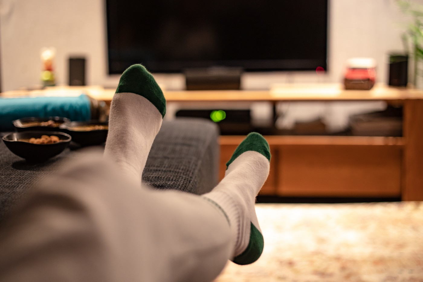 View of person's crossed legs/feet on the sofa with TV in background.
