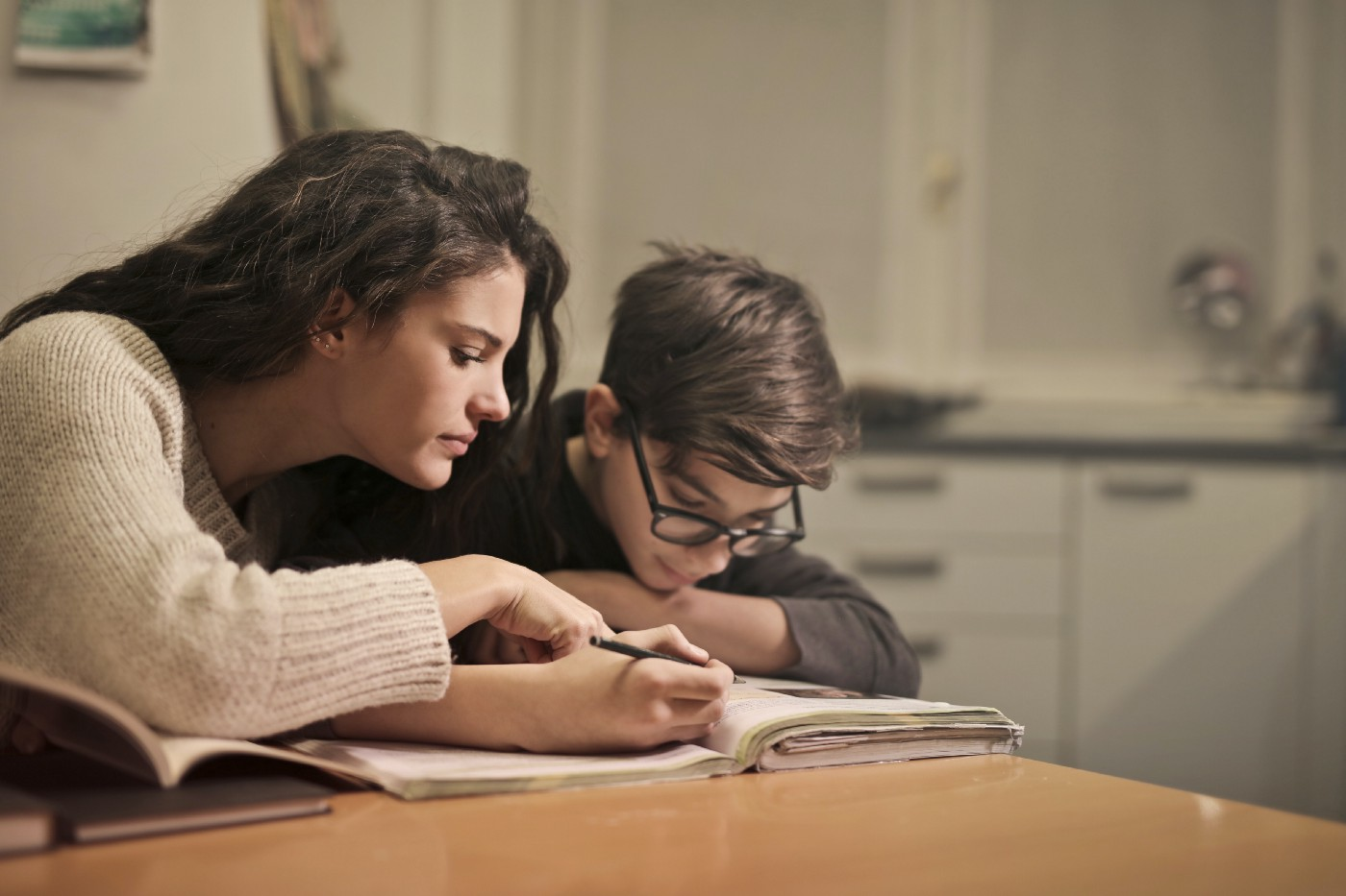 Mom leaning over and helping son who is writing in a book at their kitchen table.