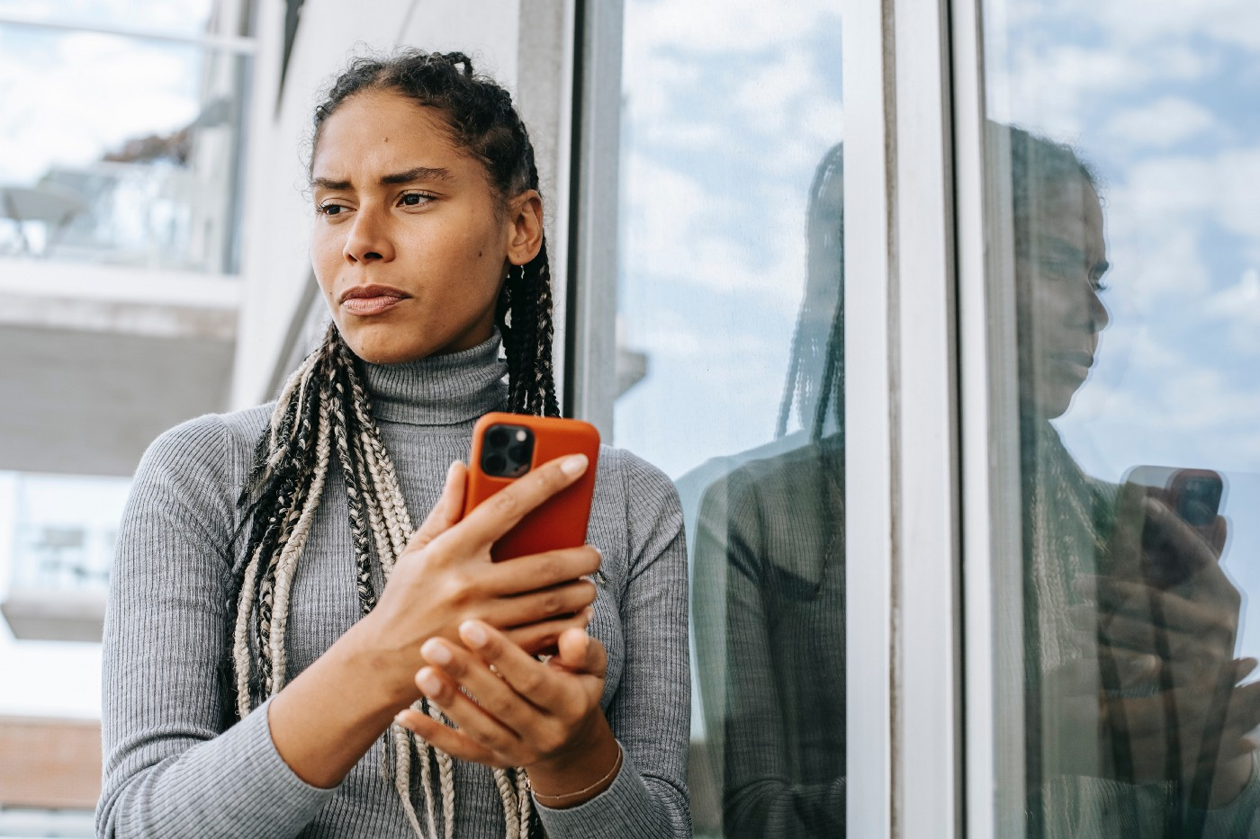 Photograph of a young Black woman with long dreadlocks wearing a gray turtleneck. She stands outside holding her phone, looking to the side, thinking.