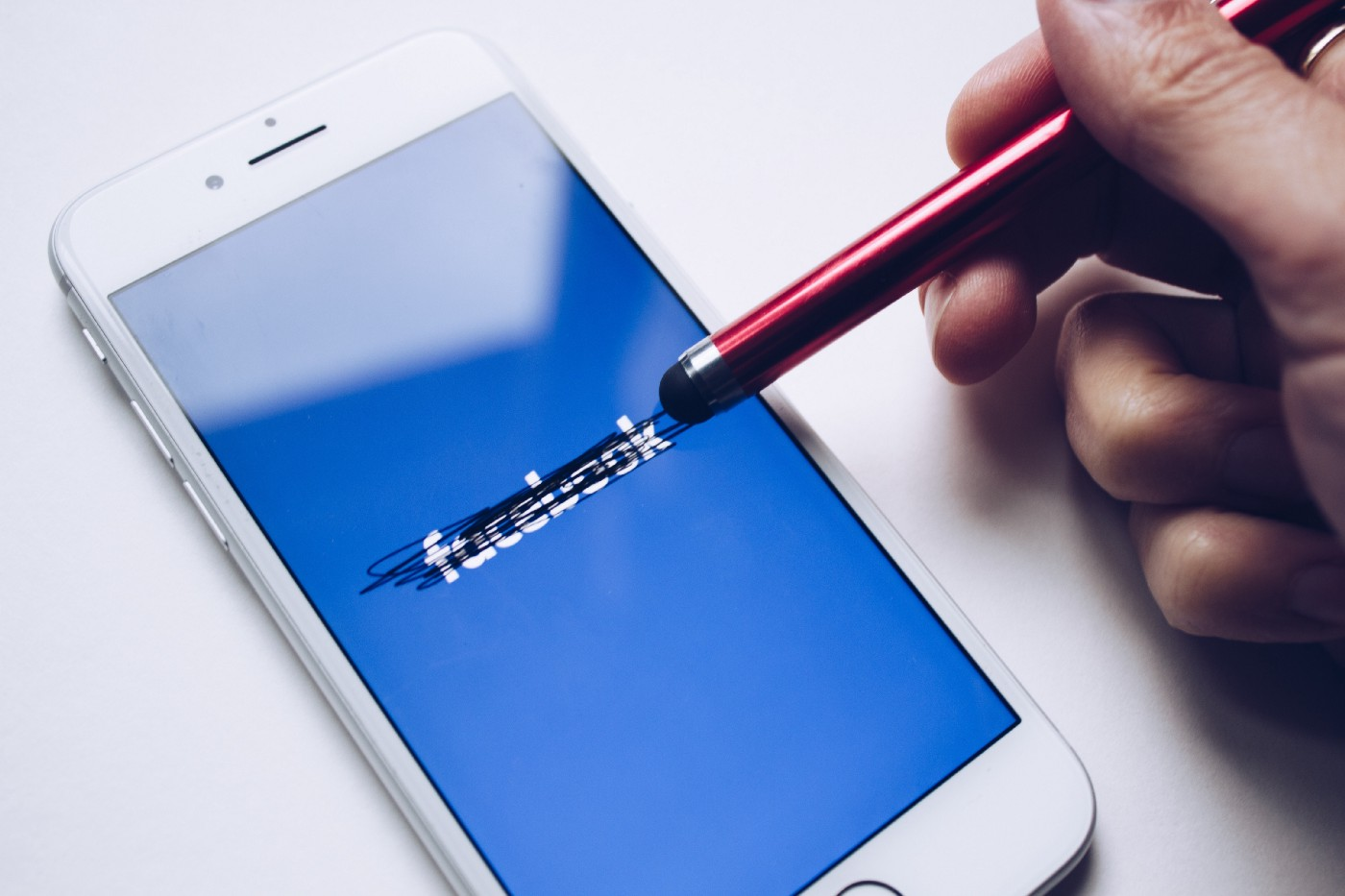 A hand scratching the Facebook logo on a smartphone using touch-sensitive pen