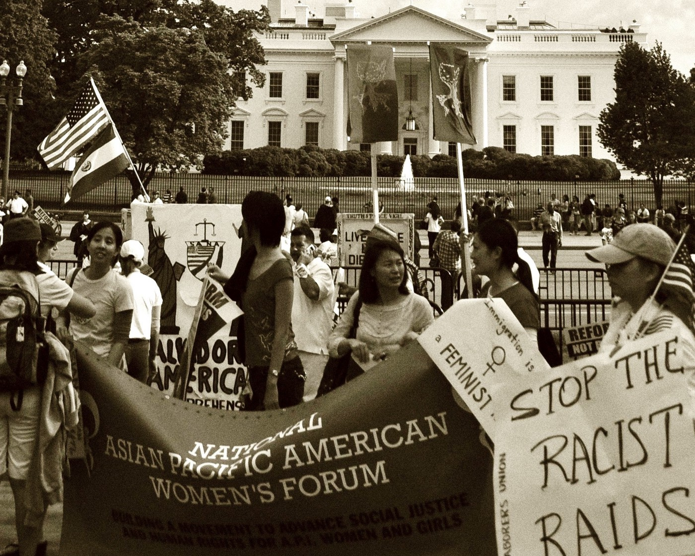 NAPAWF DC chapter holds a banner in protest of deportation raids in front of the White House in 2009.