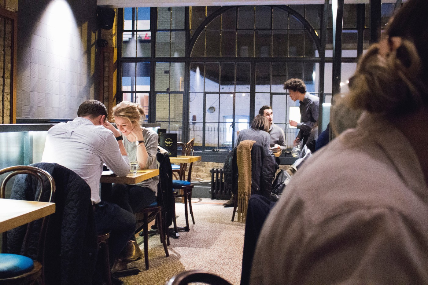 Diners and servers at tables in a busy restaurant or bar