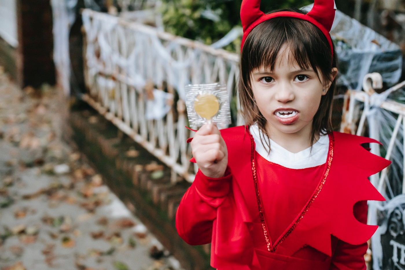 A little girl in a devil costume holds up a lollipop