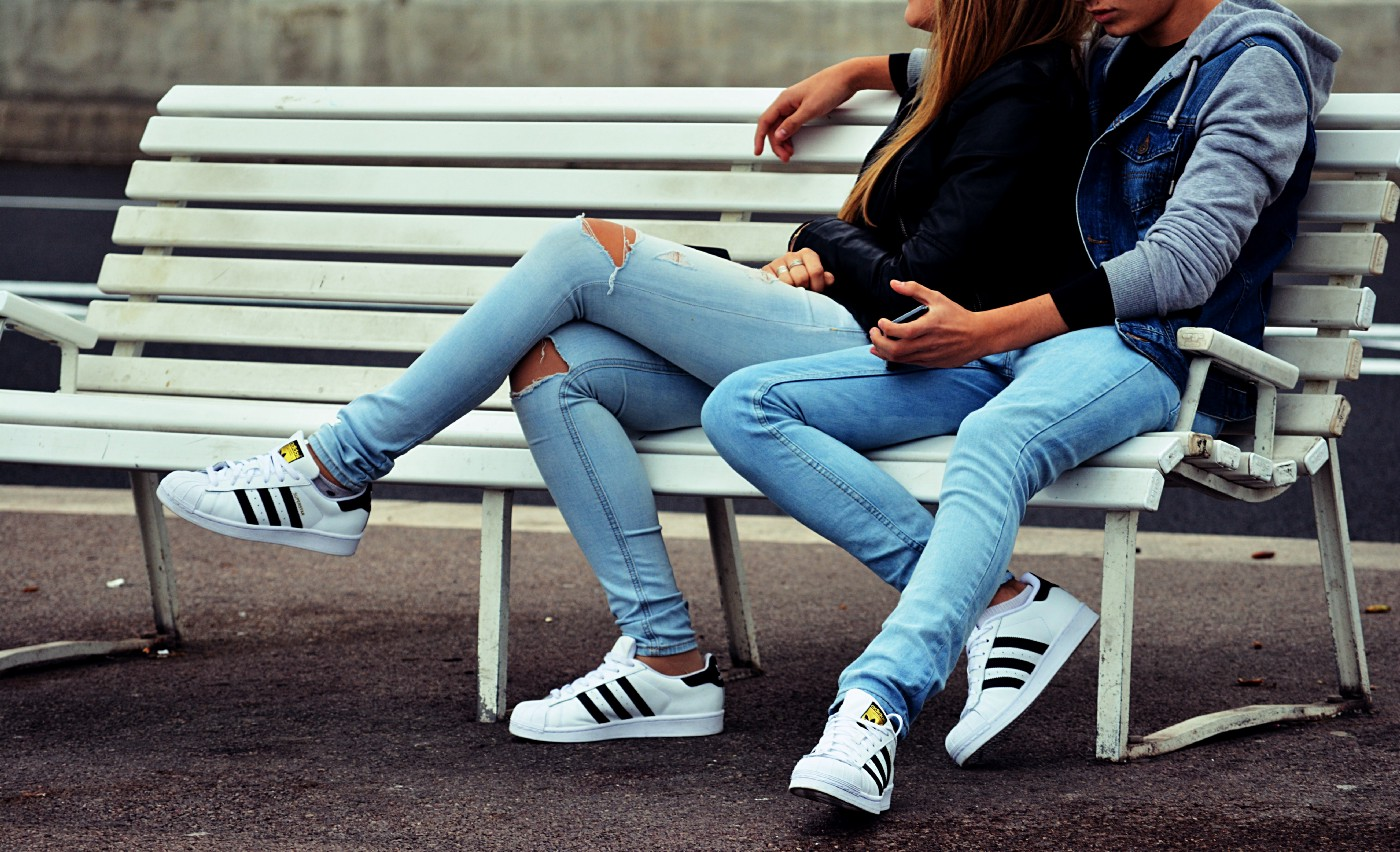 male and female young persons sitting on a bench