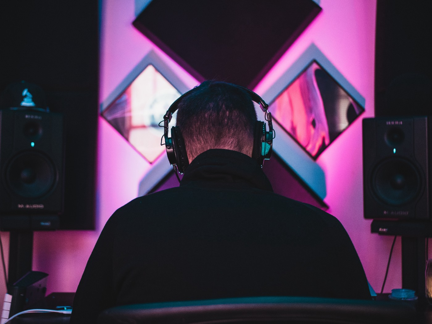 High contrast photo in blacks and neon pinks of the back of a person's head and shoulders. They are wearing headphones and large audio equipment is visible in the background.