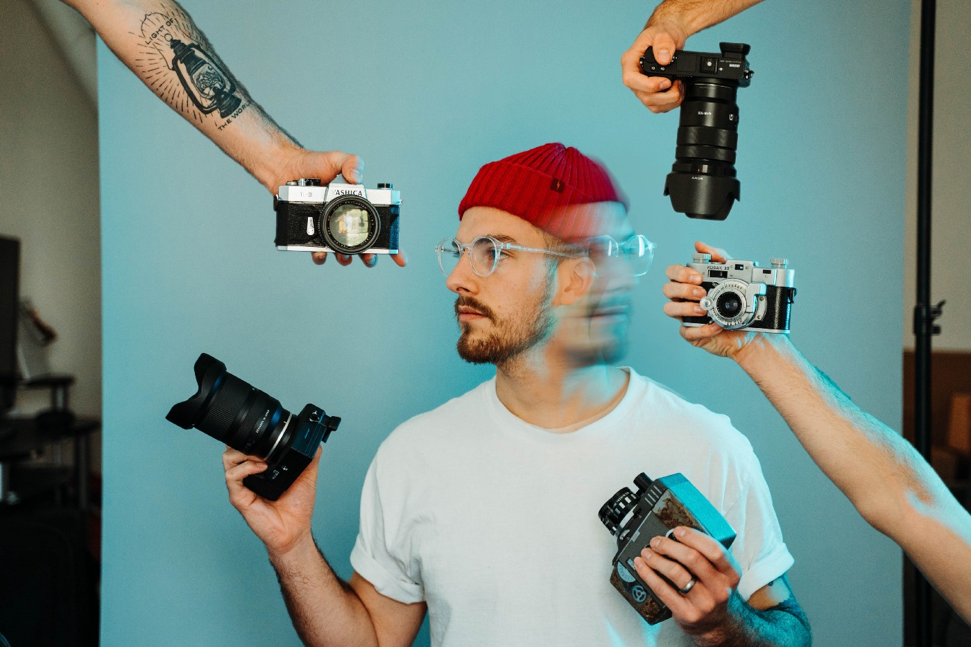 Man with red beanie can't decide what camera to use
