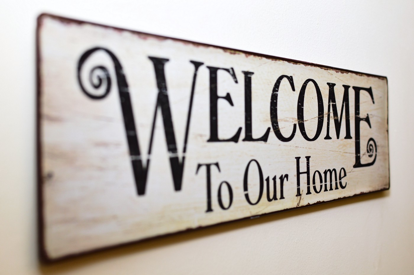 """Welcome to Our Home"" brown print on white, worn wood with dark letters."