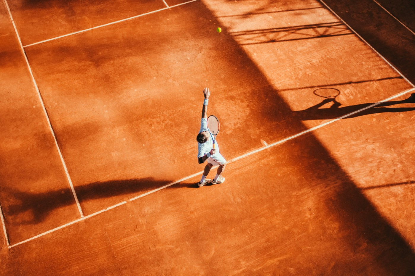 A person playing tennis on an orange court.