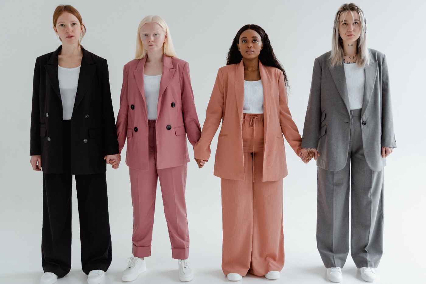4 Women Standing Side by Side Wearing Blazers of various colors against a white background.