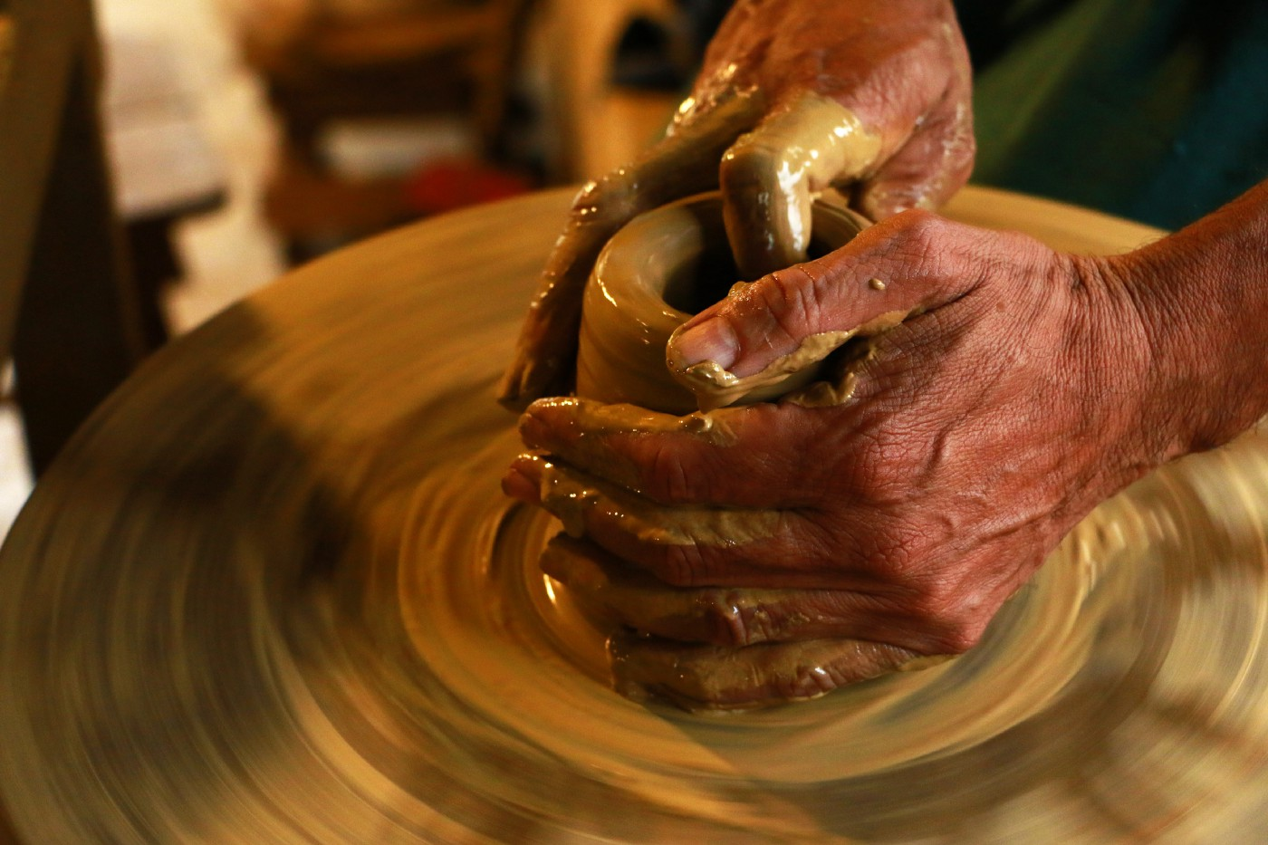 Image of a potter's hands giving shape to clay