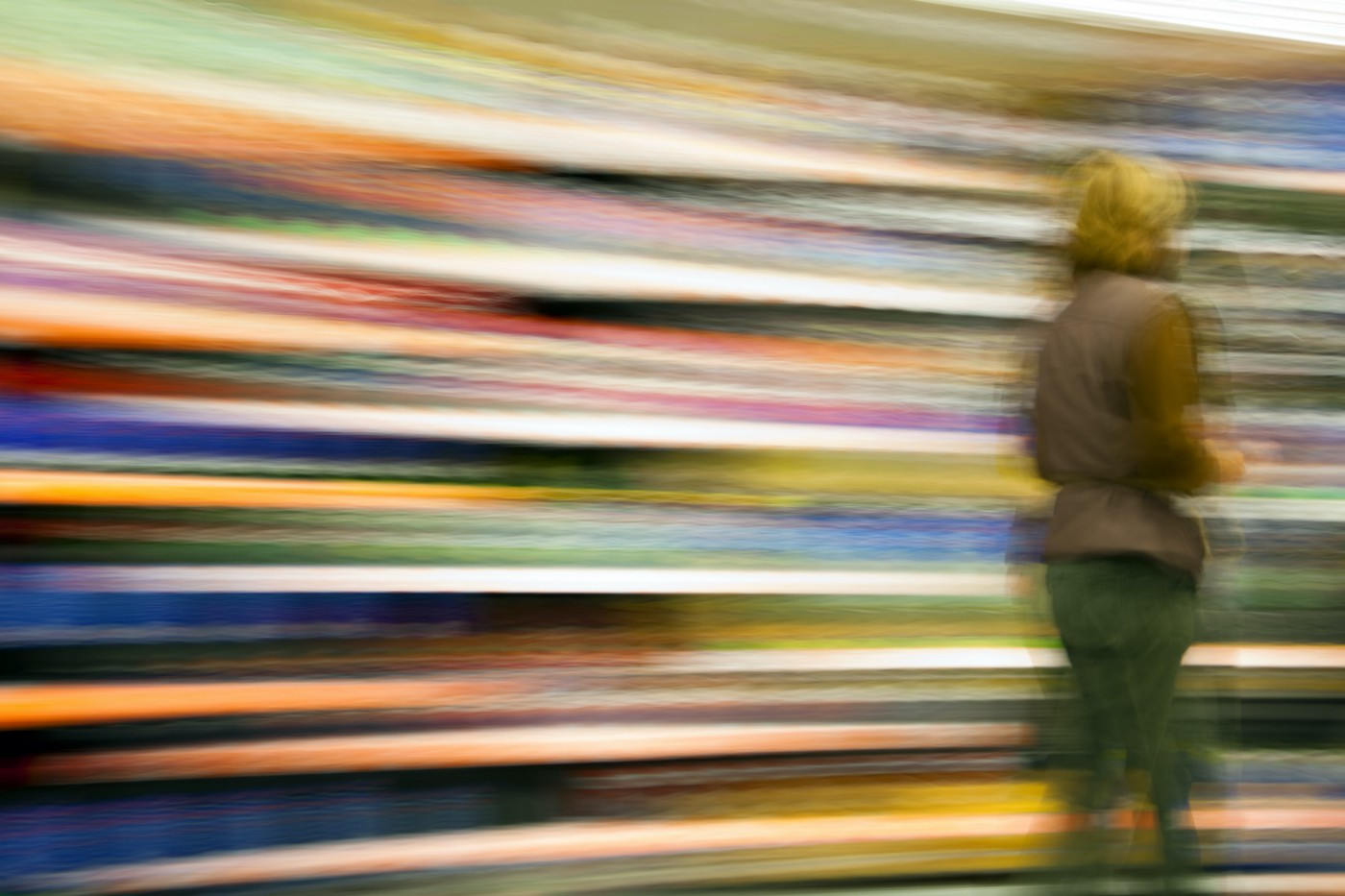 A person walking toward the right side of the pic against a colorful, motion-blurred background.