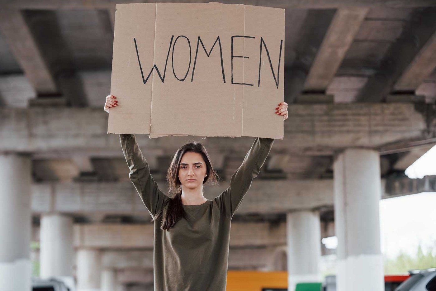 A woman stands beneath an overpass. With her hands, she's holding high a cardboard sign with the word WOMEN on it.