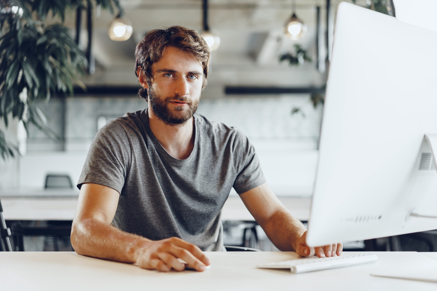 Contented male freelancer in grey t-shirt sitting at the computer with hand poised over the mouse, in a light, airy working space,