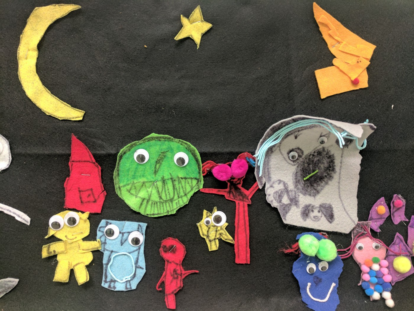 A child's felt storyboard with various characters made of felt with googly eyes glued on.