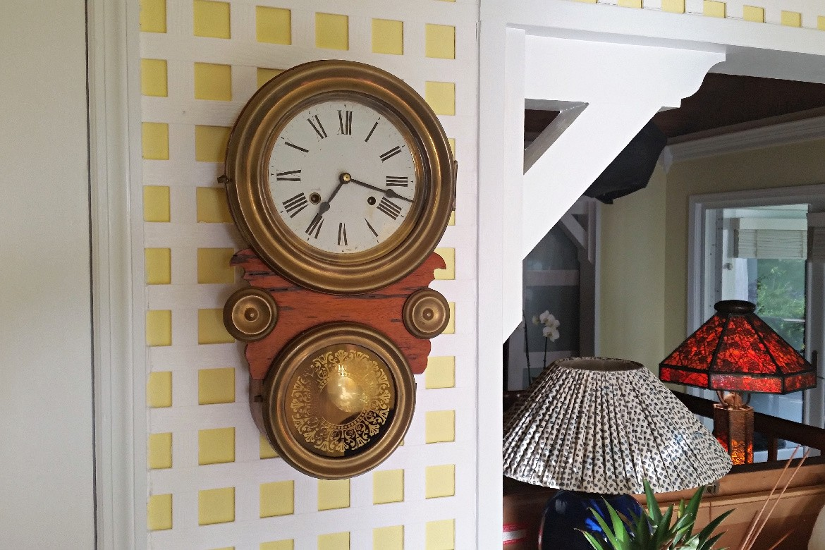 Wind-up antique wall clock—large round dial on top and smaller round window below with swinging pendulum