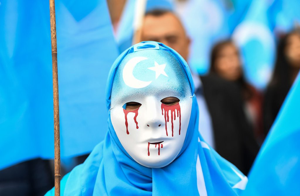 Woman with a blue hijab and a full face mask with red tears dripping from the eyes and mouth