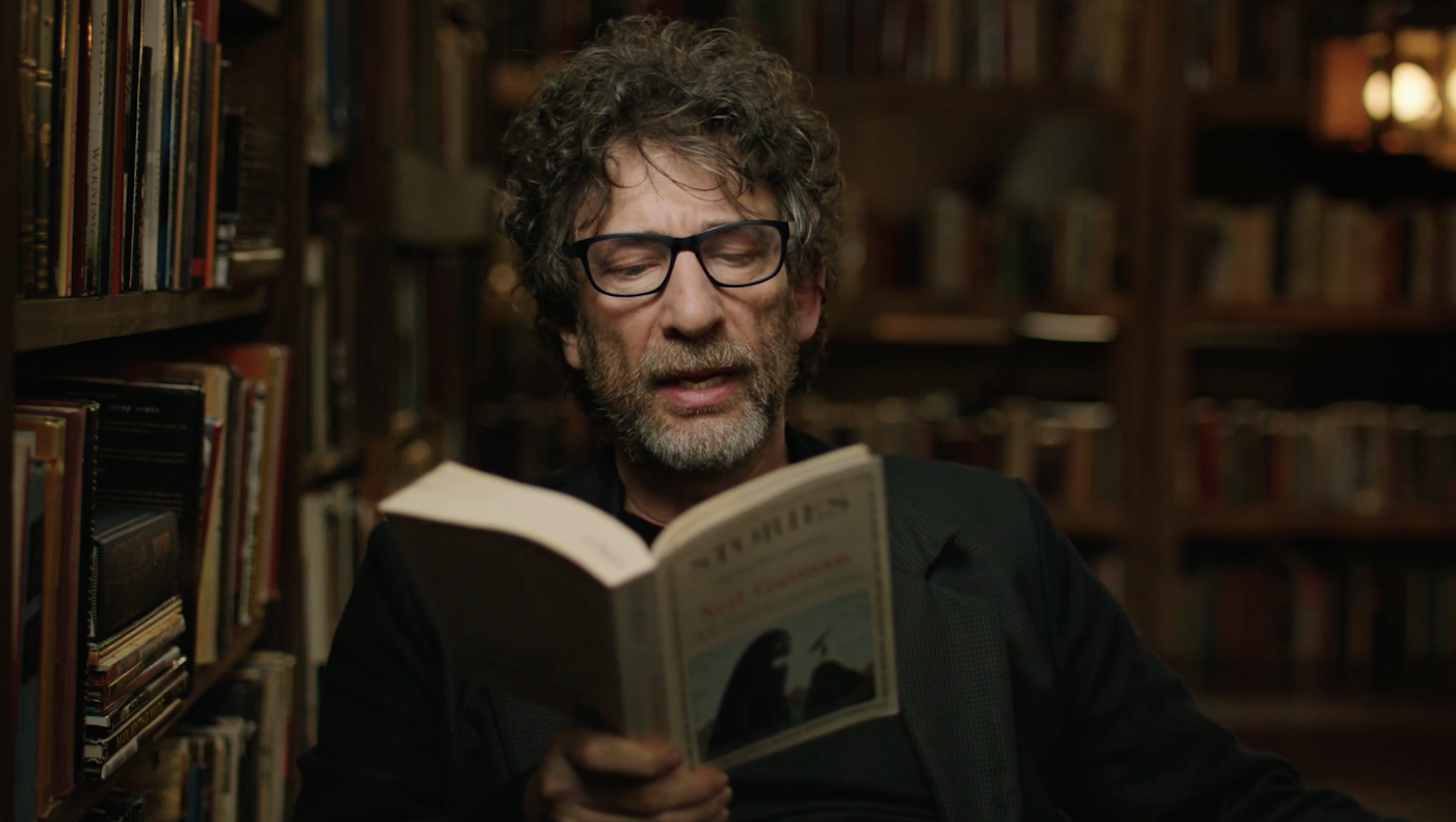 Neil Gaiman reading from one of his short stories to audience. He is wearing Black t-shirt with black suit.