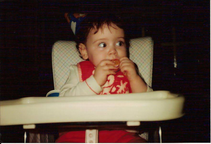 a baby sits in a retro-looking highchair with a party hat on and she's biting into an orange segment with apparent trepidation
