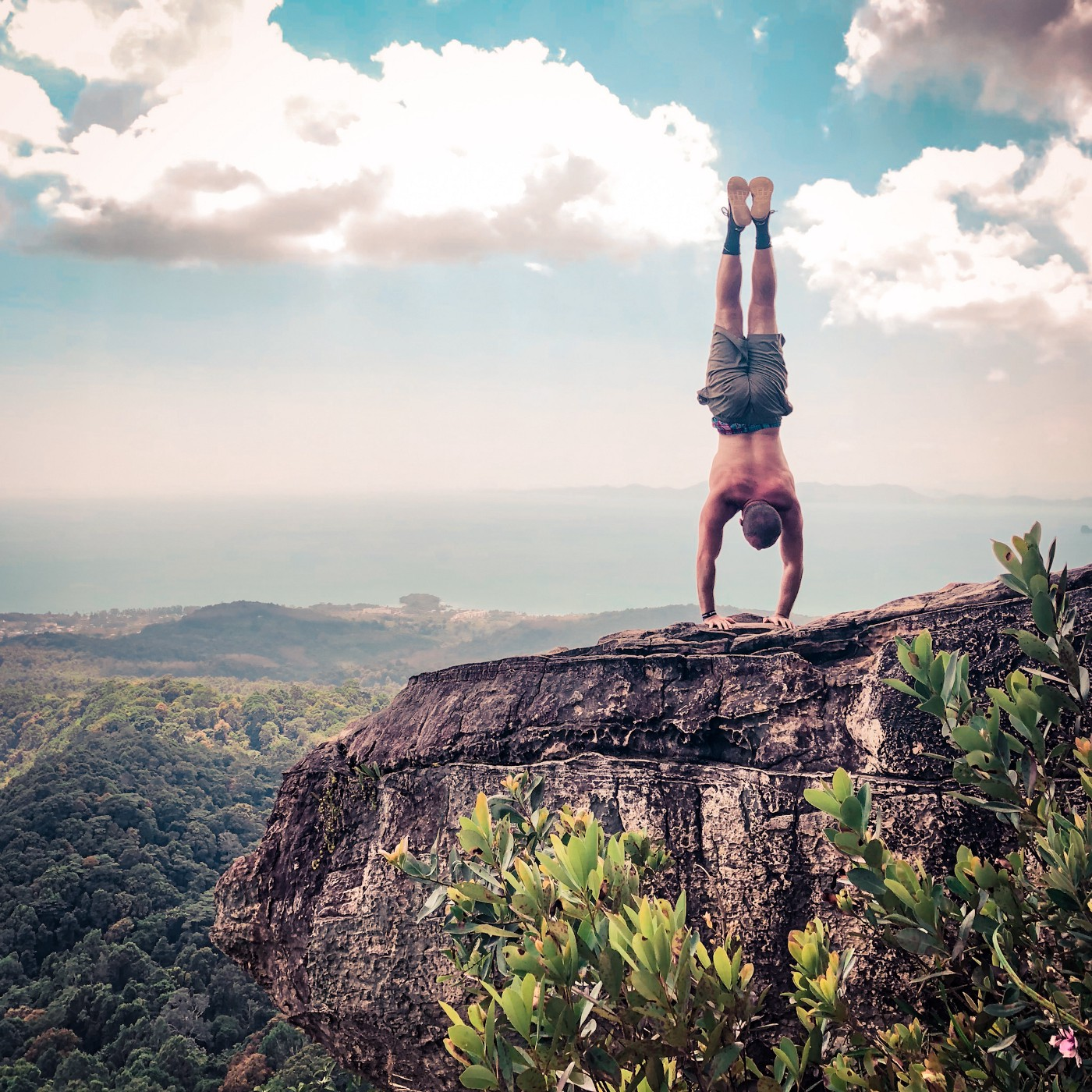 How to instantly improve your handstand header image. The author doing a handstand on the edge of a cliff in Krabi, Thailand.