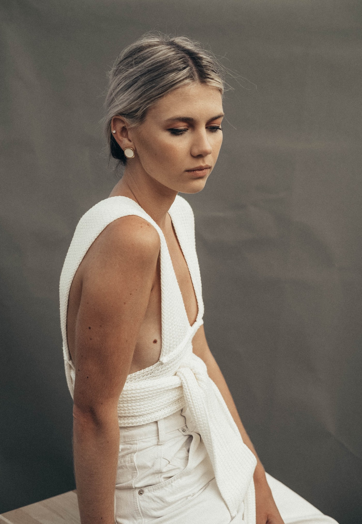 Young blonde woman in white dress looking sad.