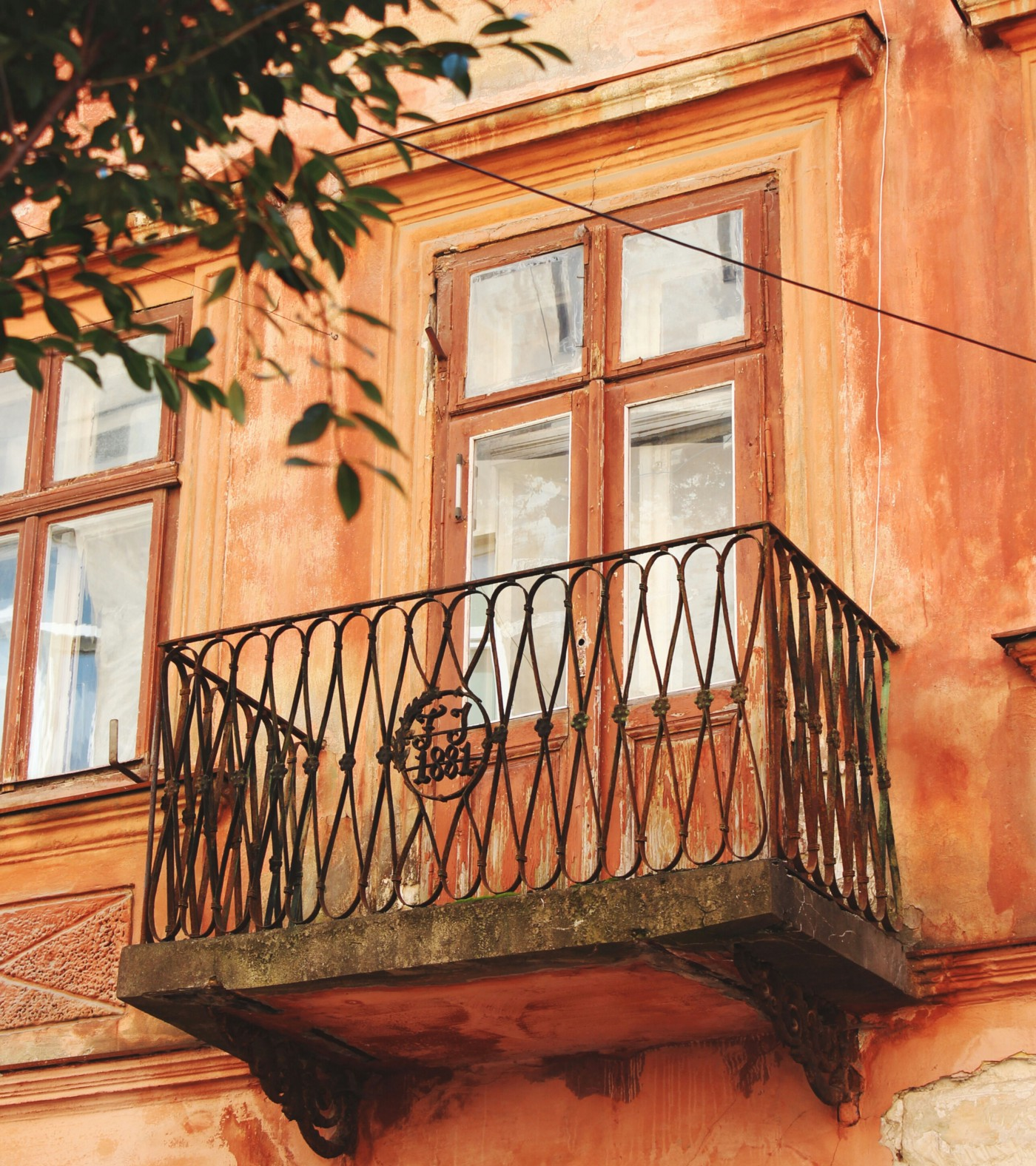 A wrought iron balcony on the upper floor of a mottled terra cotta colored building with tree leaves in the upper left corner