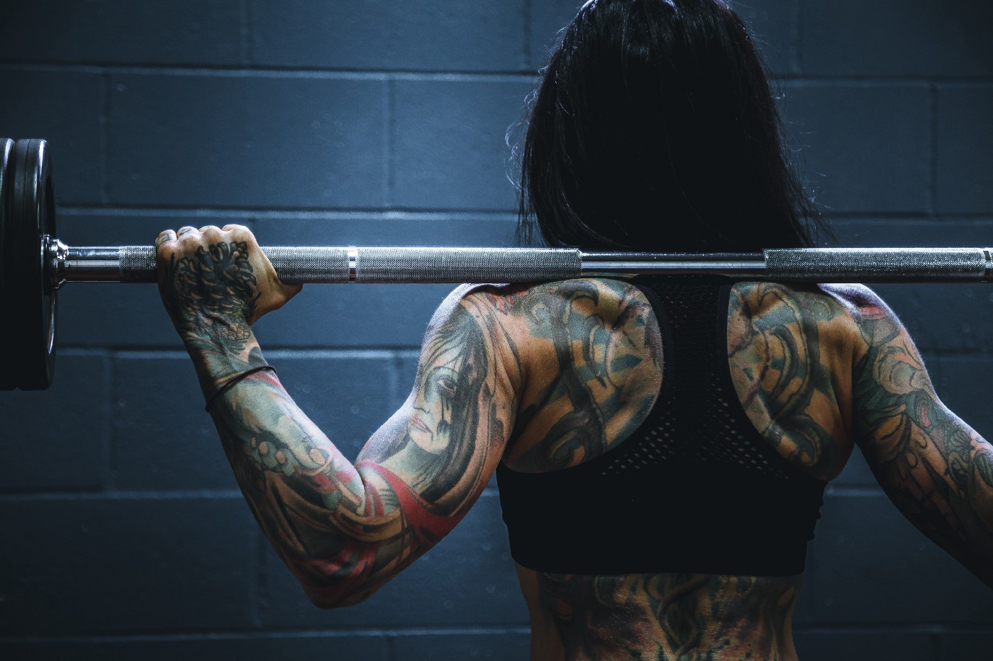 A woman covered in tattoos lifting a barbell with heavy weights on it on her back