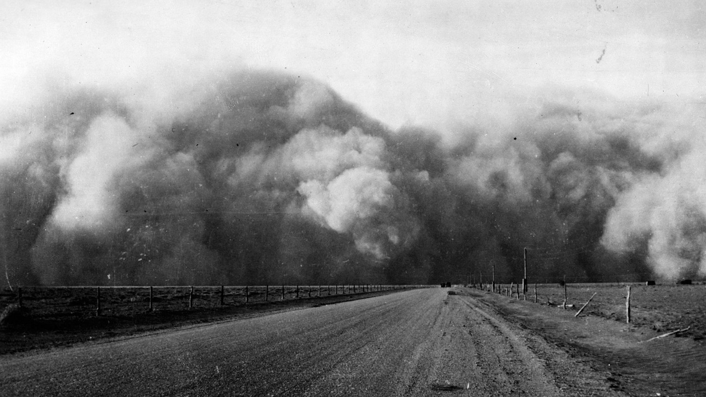 An antique photo of a dust cloud approaching the camera over a dirt road with barren fields to either side.