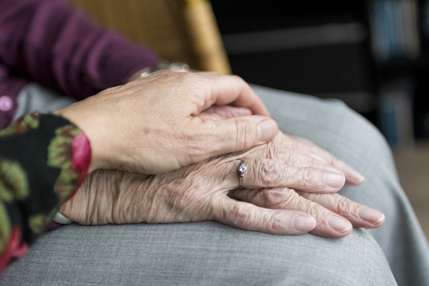 A woman's hand covers the wrinkled hand of her elderly mother.