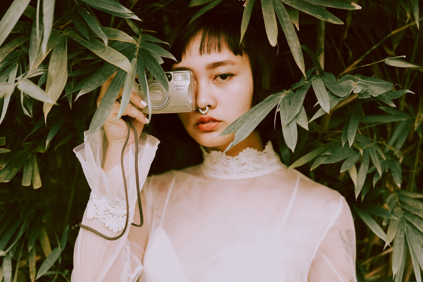A woman with short black hair wearing a white translucent long sleeve top with lace detail holding a camera to one eye against a green leafy background