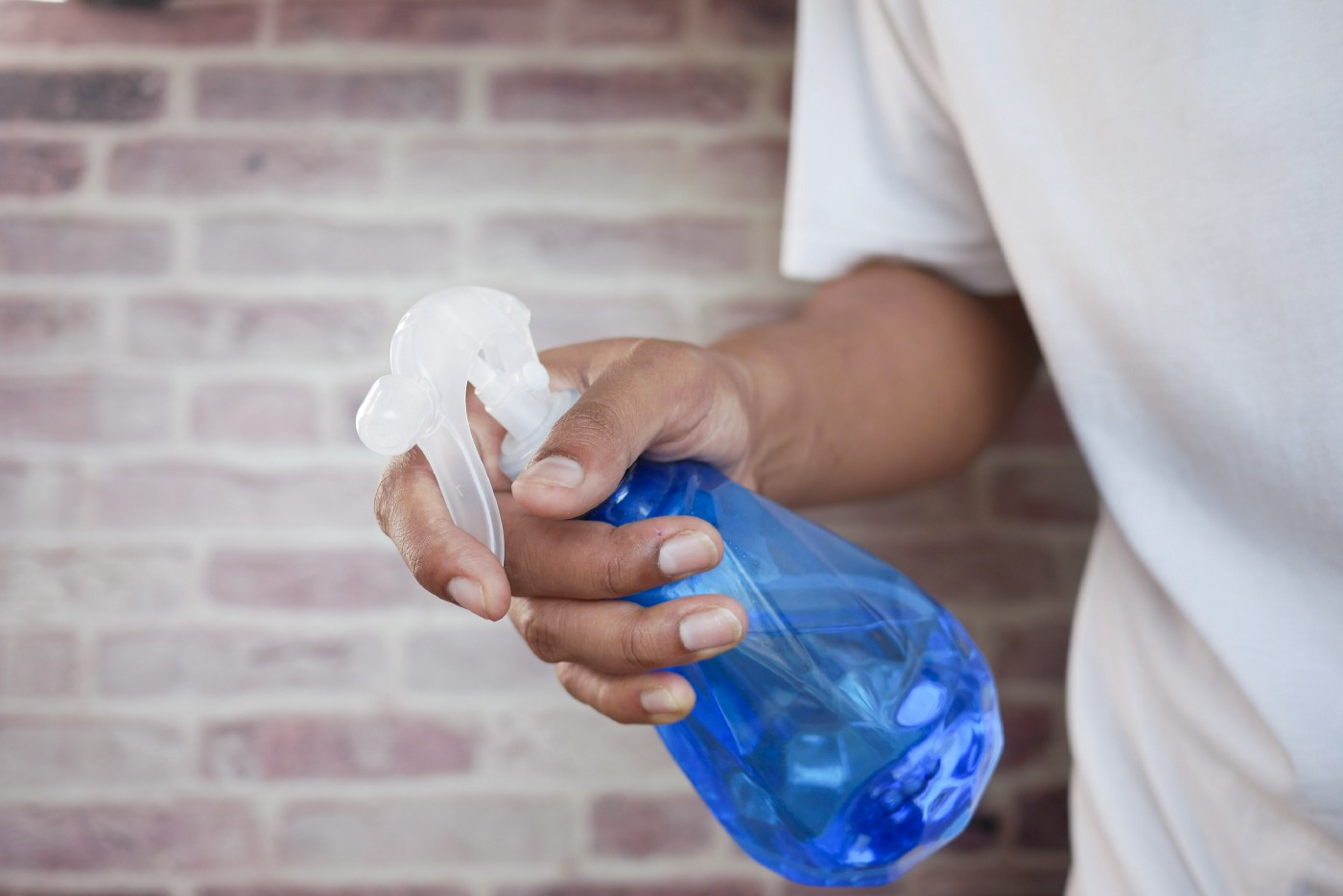 Unsplash stock photo showing a person's hand holding a spray bottle filled with blue cleaning liquid.