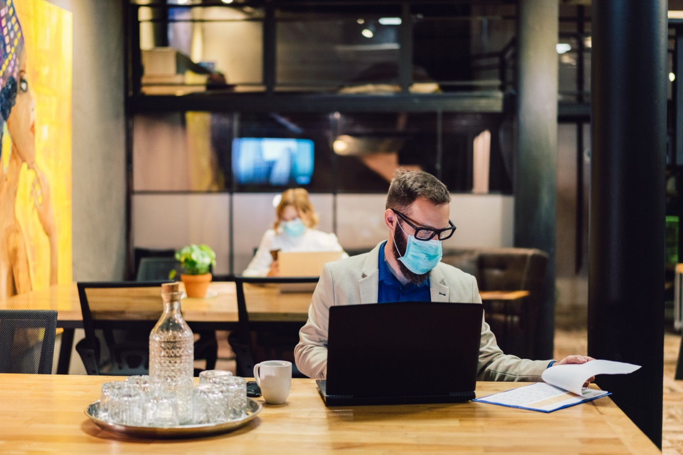 Businesspeople wearing masks in the office and sitting at further distances.
