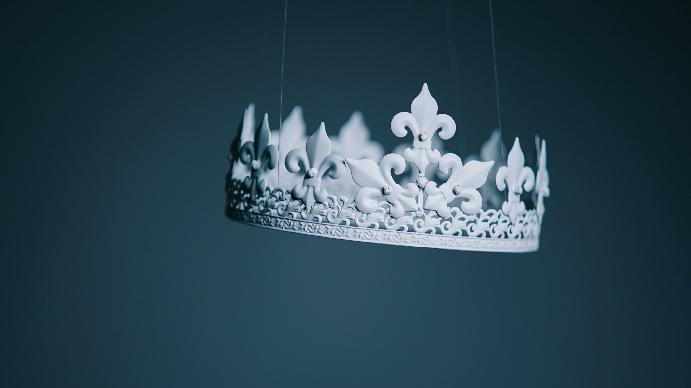 An ivory crown dangling by narrow threads.