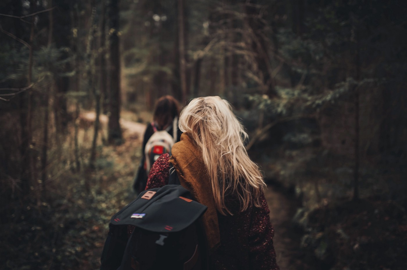 Two girls with backpacks walking through the forest. One girl has blonde hair and wears a brown scarf