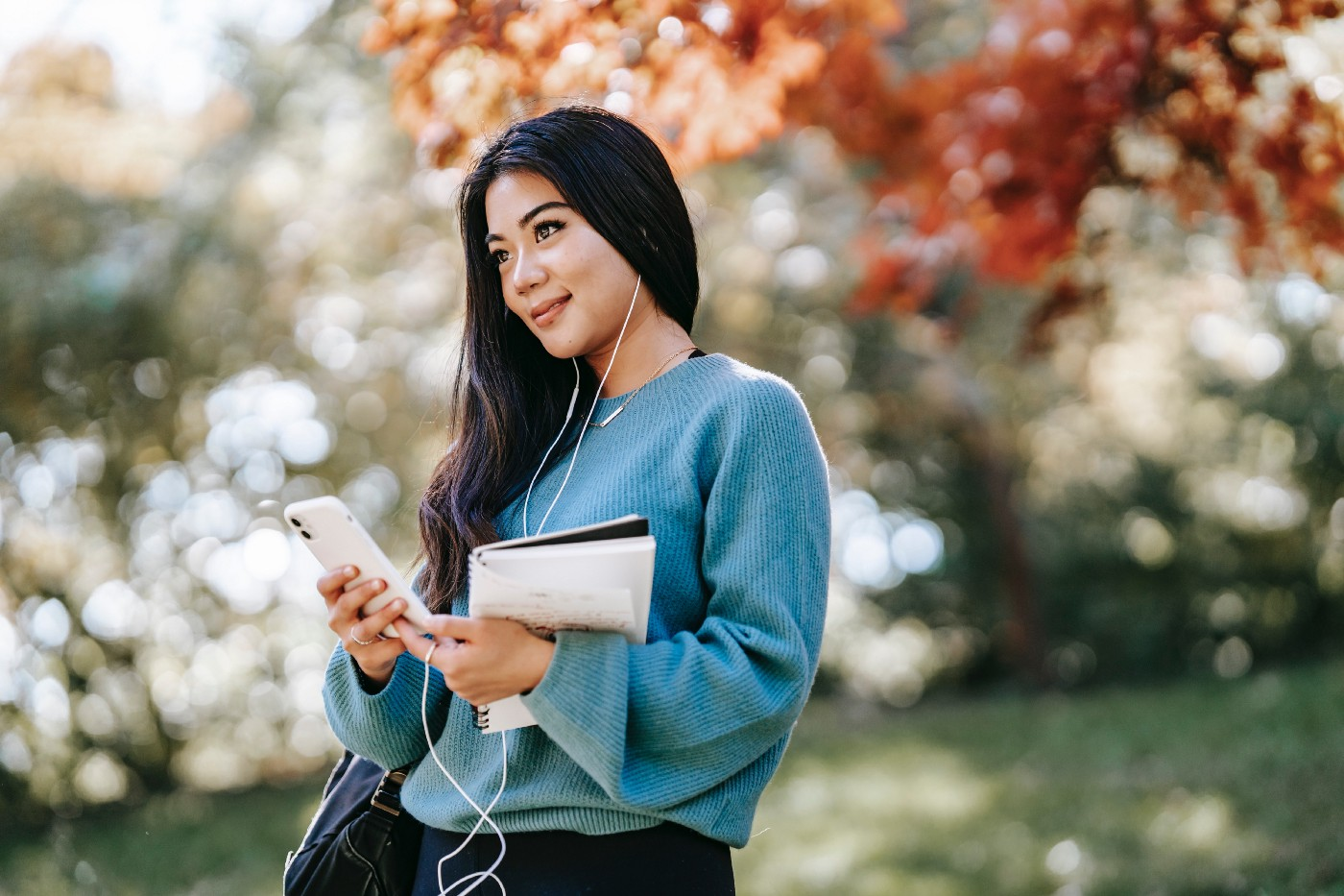 Woman using phone and headphones to audio journal outside