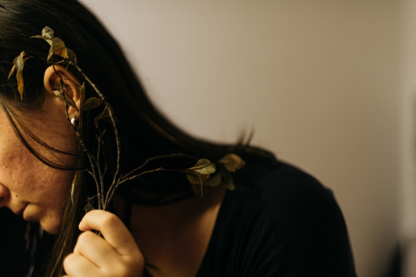 Self-portrait of a girl with flower branches in her hands close to one of herear—Still life photographer Bozen, Italy
