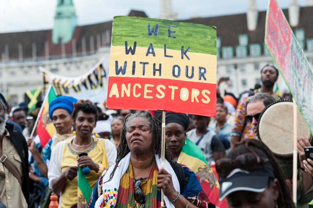 "Photo of an Emancipation Day march in London, one woman carries a sign that says ""WE WALK WITH OUR ANCESTORS."""