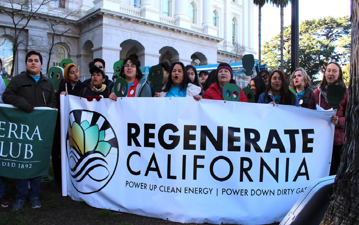 """People line up behind a banner that reads """"Regenerate California."""""""