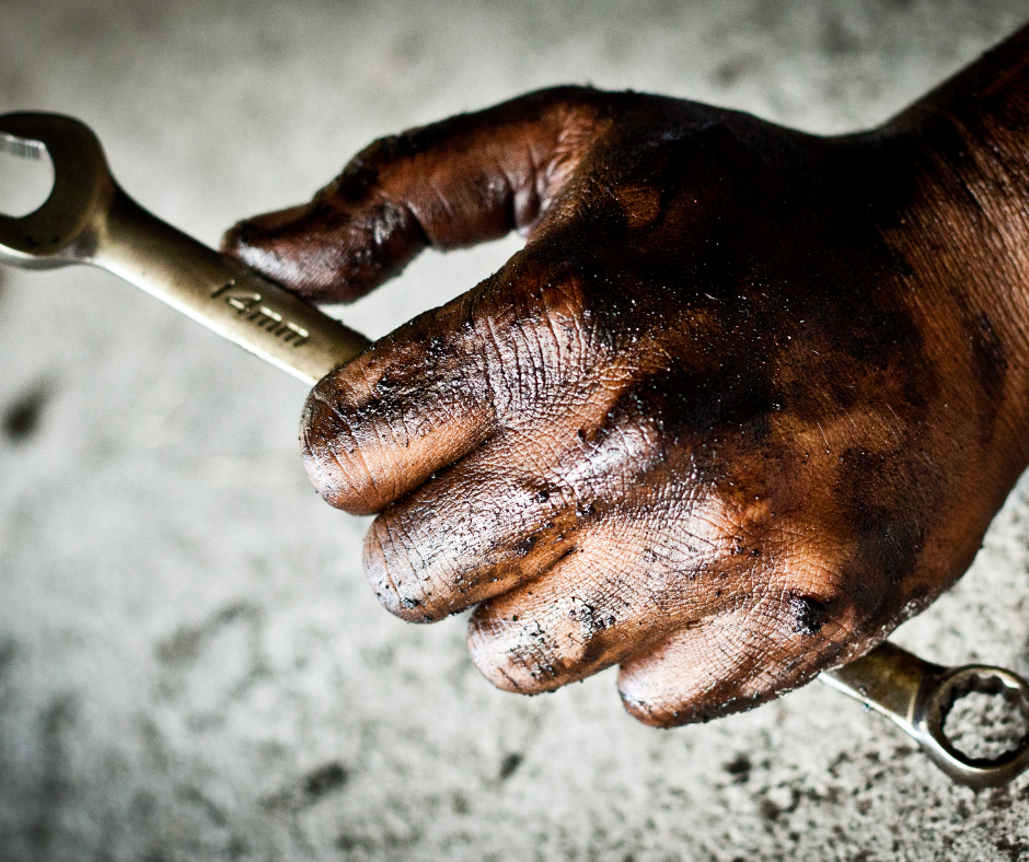 Greasy Mechanic Hand holding a wrench