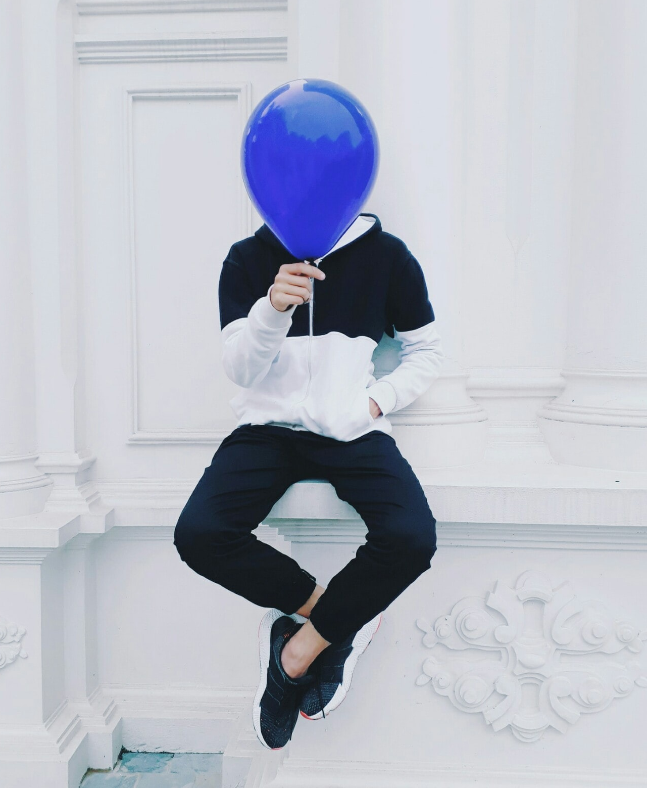 A man holding a blue ballon which covers his face.