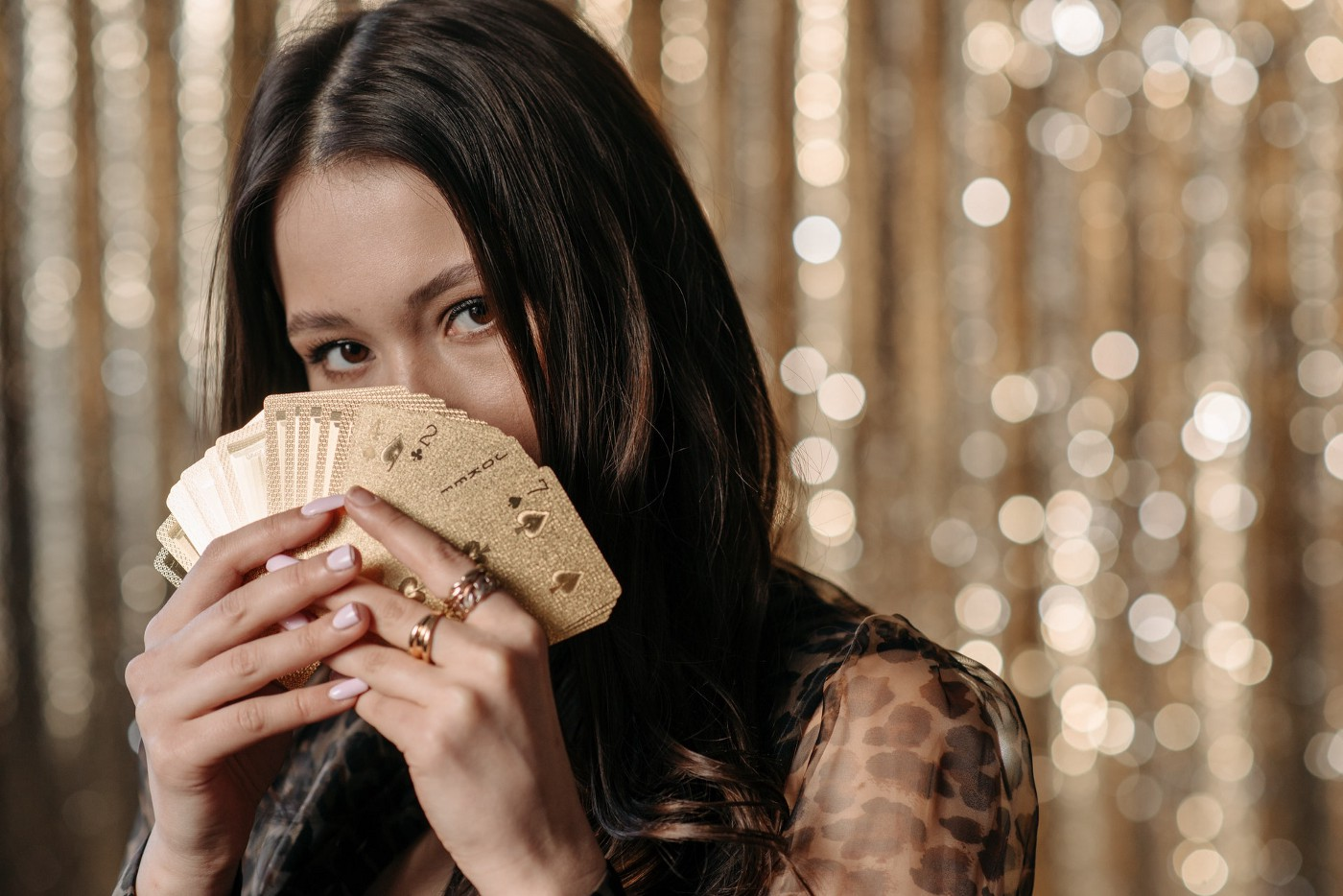 A woman holding a deck of golden playing cards.