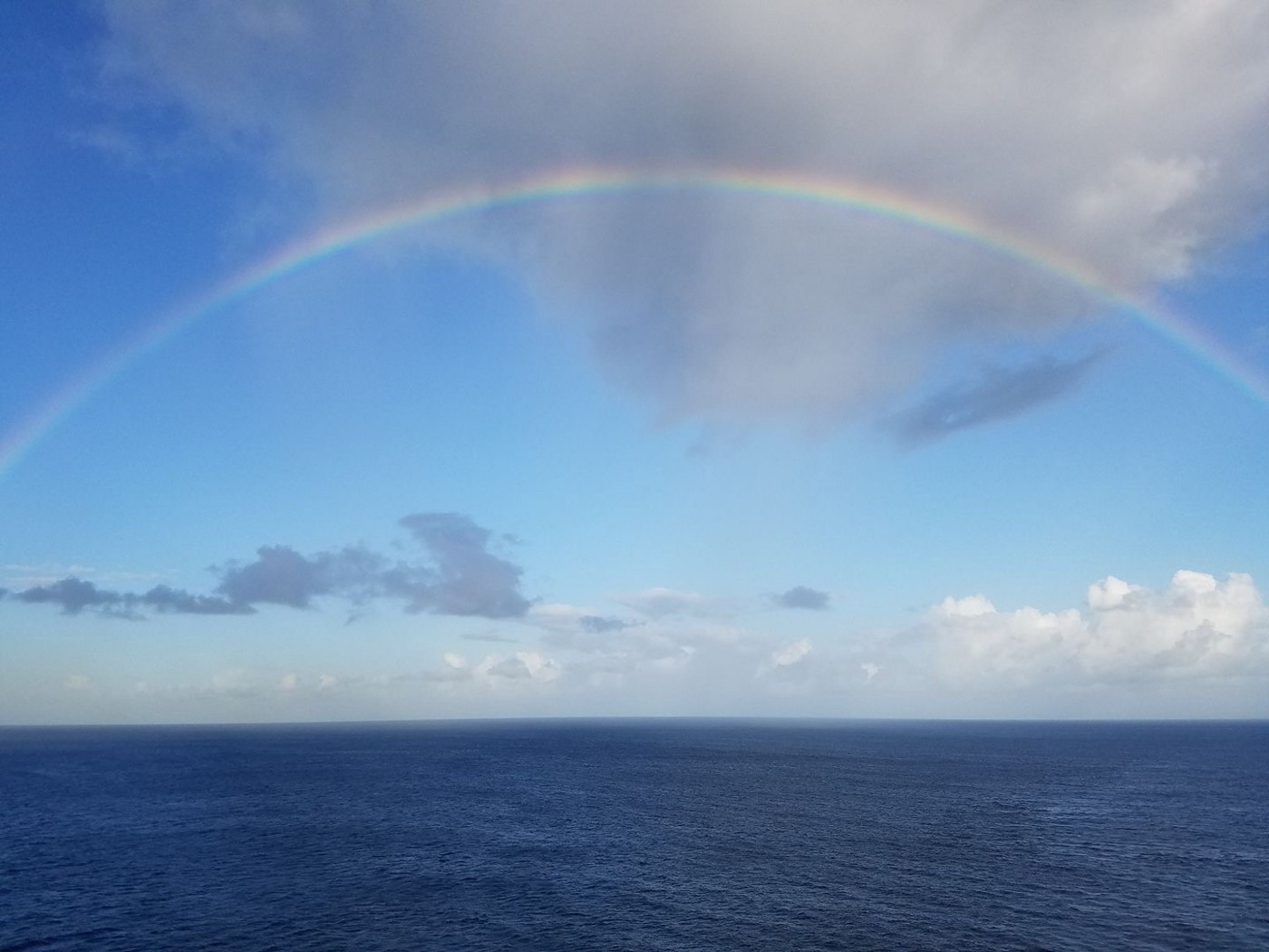 A full rainbow, over open water.