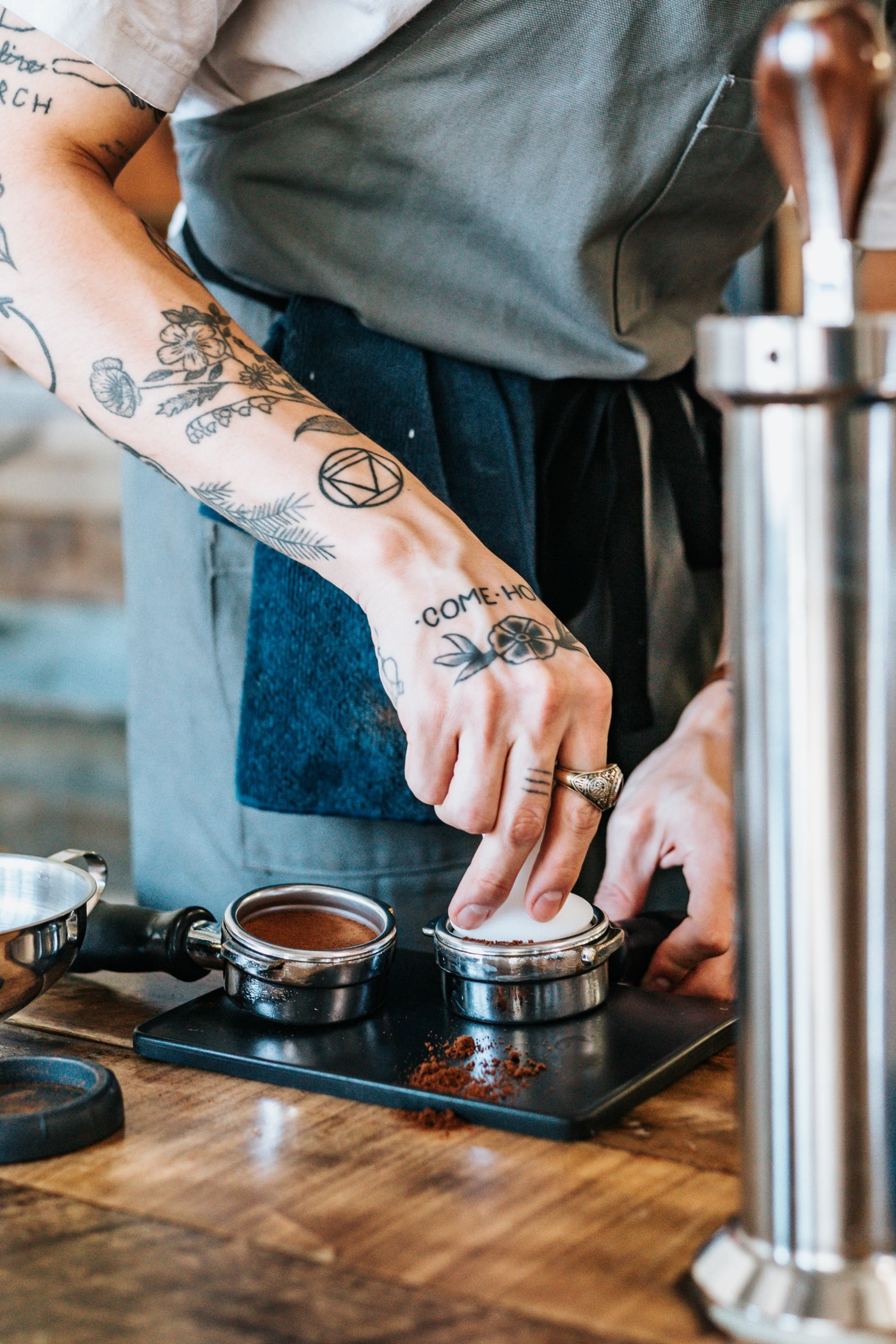 Person with tattoo, making coffee