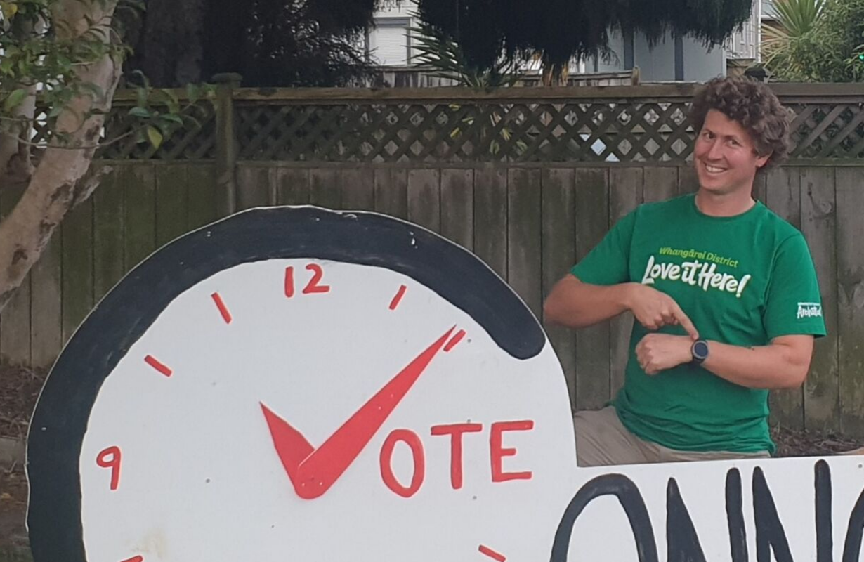 Nicolas is behind a sign with an image of a clock and the words 'vote Connop'; he's smiling and pointing at his watch.