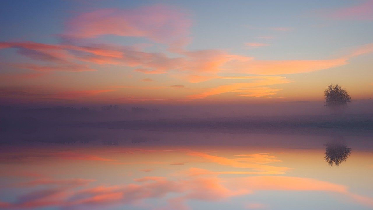Sunrise with light peach colors, pink and laveder in sky and reflected on bay.