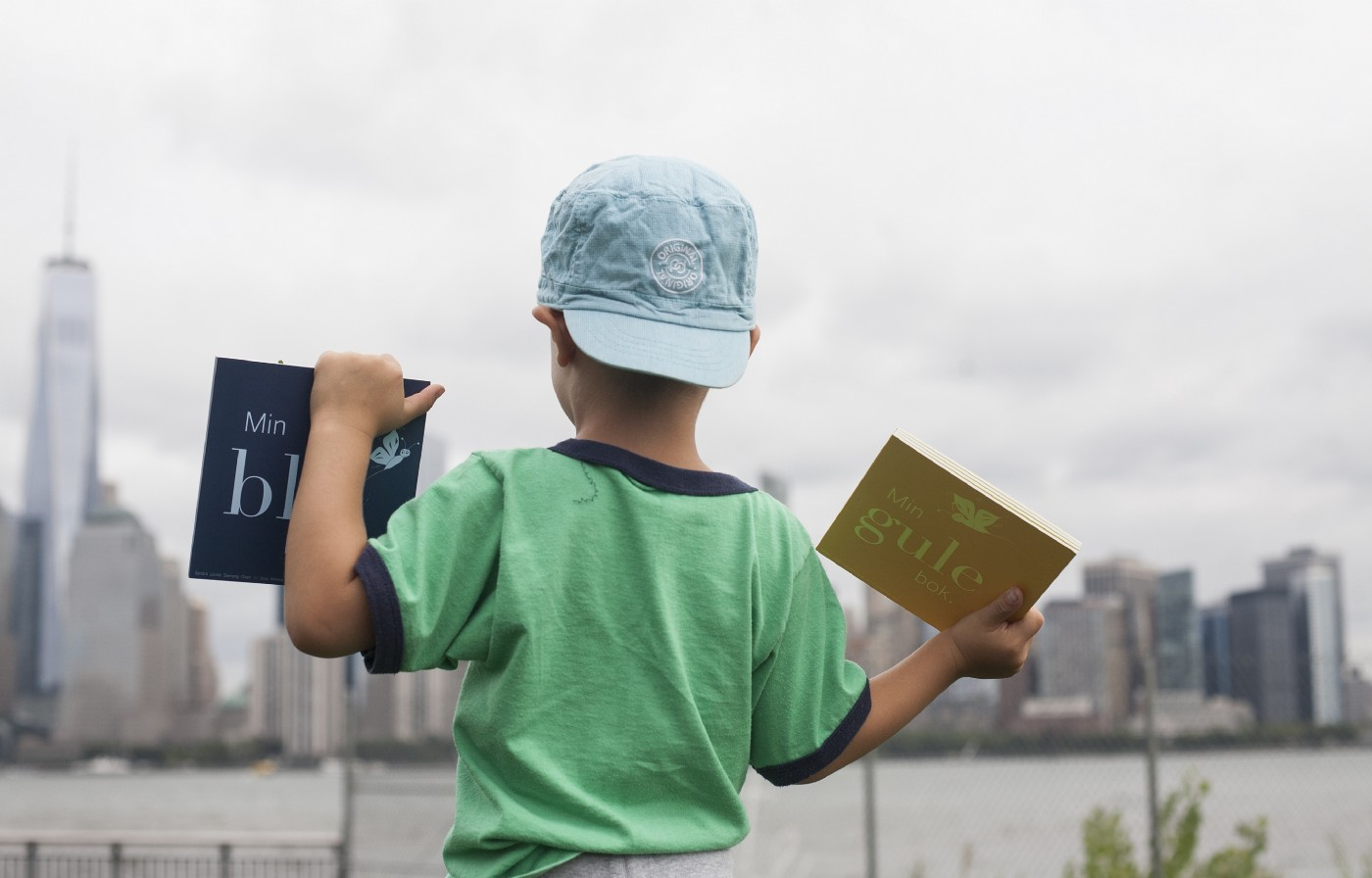 Image of male child holding up books