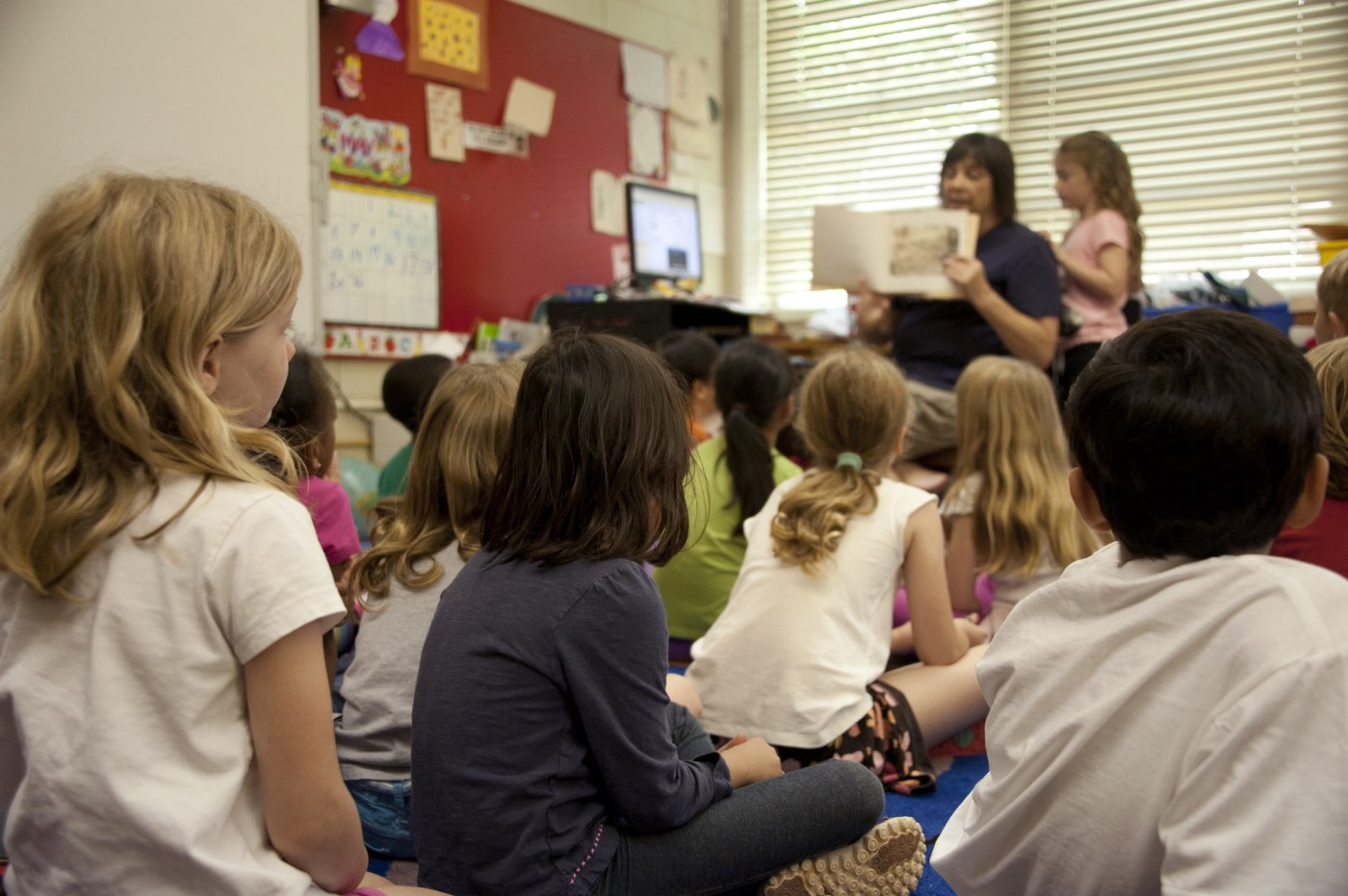 Children in a classroom being read to by a teacher.