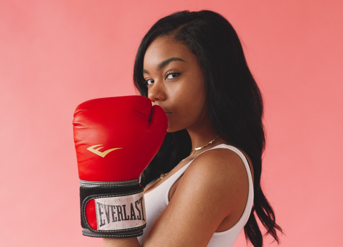 A young woman wearing Everlast boxing gloves looking into the camera lens