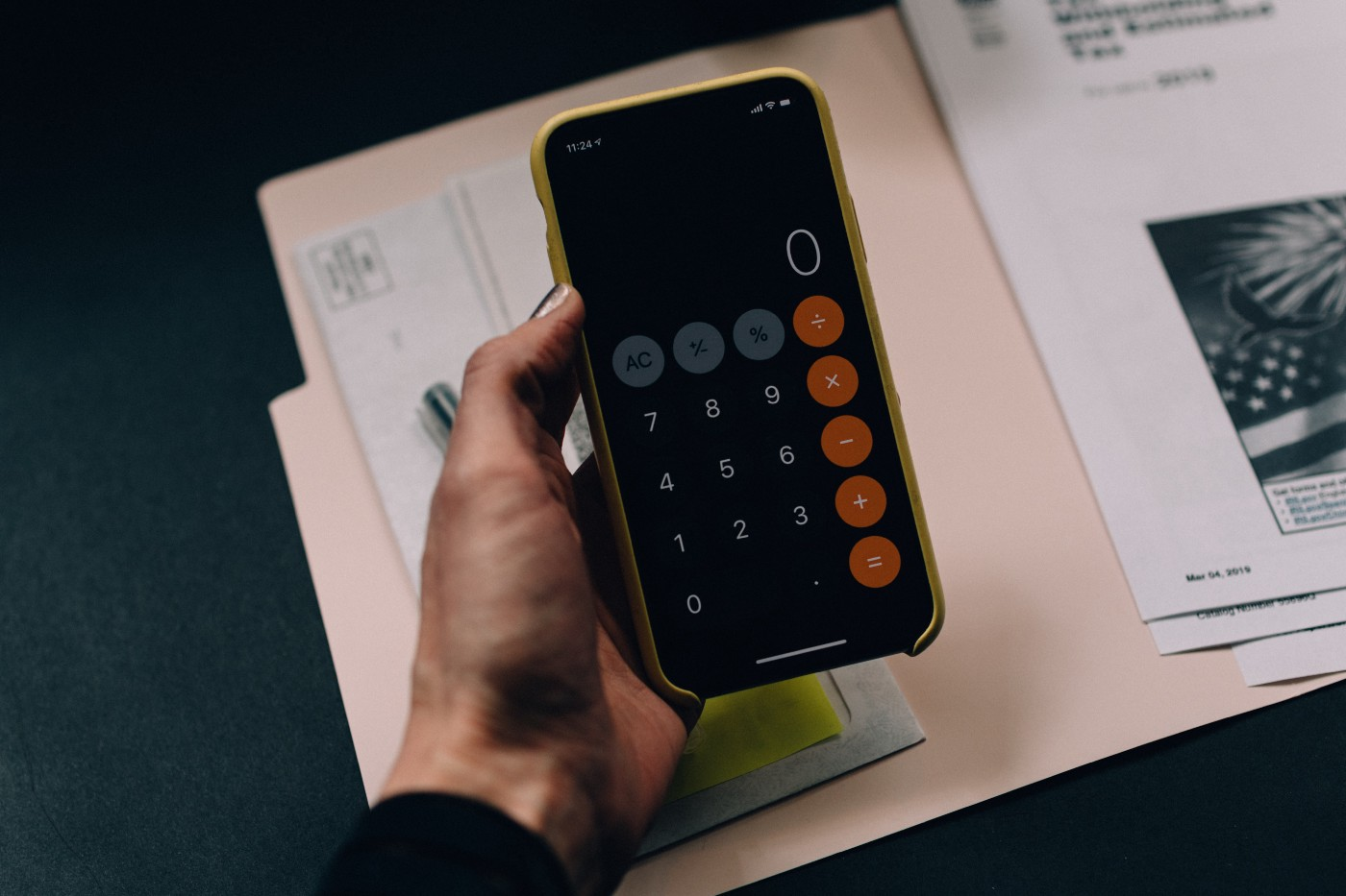Hand holding Android phone with calculator app running over manila file folder with papers